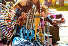 An Indian From South America Dances In A National Costume With Feathers.