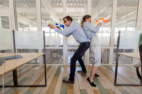 Fotografía  Man and woman in formal outfits standing back to back and aiming toy guns while