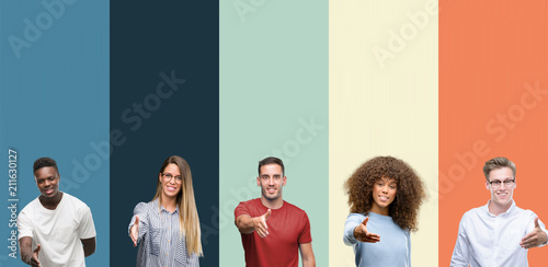 Obraz na plátně Group of people over vintage colors background smiling friendly offering handshake as greeting and welcoming