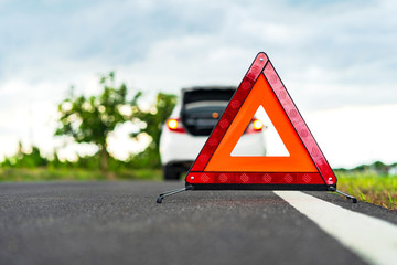 Problems car and a red triangle warning sign on the road