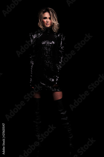 f2568de54e8 mysterious woman in glistening black dress and long boots standing ...