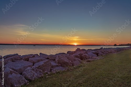 Spoed Foto op Canvas Zee zonsondergang Sunset over Lake with a Rock Shoreline