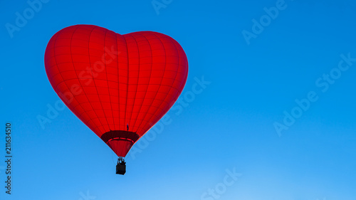 Fotografie, Obraz Bright red hot air balloon in the shape of heart against blue sk
