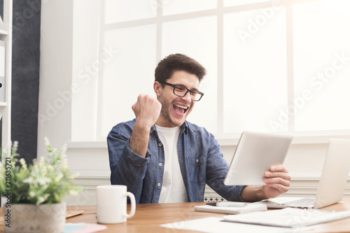 Fotografía  Young happy businessman in office with tablet