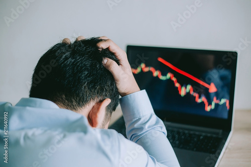 Stress Business man look at to the laptop show financial market chart graphic going down Fototapeta