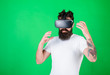 canvas print picture - Man with beard in VR glasses, green background. Hipster on busy face exploring virtual reality with gadget. Interactive surface concept. Guy with head mounted display interact in virtual reality