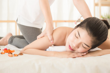 Obraz na płótnie Canvas Young asian woman enjoying relaxing back massage in spa. Body care, skin care, wellness, alternative medicine and relaxation Concept.