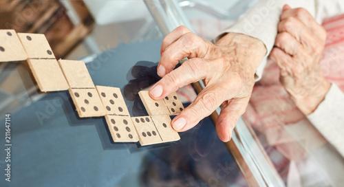 фотография  Hände von Senioren legen Spielsteine beim Domino