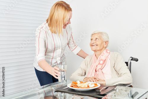 Fotografía  Pflegedienst Frau serviert alter Frau ein Essen