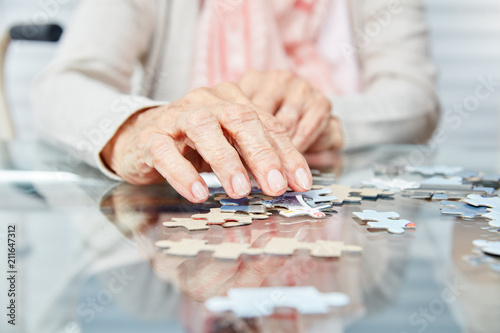 Foto  Hände von Senioren beim Puzzle spielen