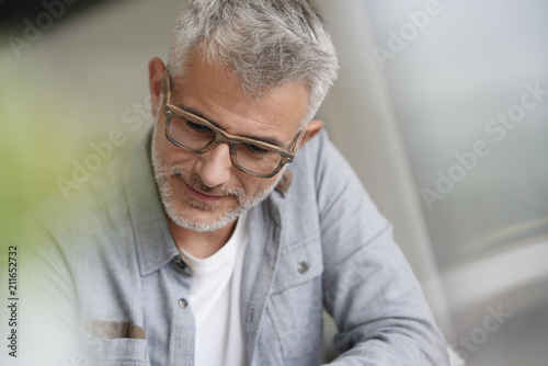 f6771428fb Middle-aged guy with trendy eyeglasses reading magazine - Buy this ...