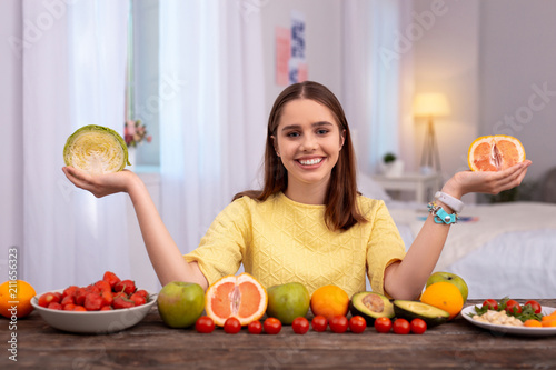 Papiers peints Echelle de hauteur Fruit or vegetable. Merry teen girl rising vegetables looking at camera
