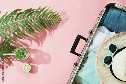 Photo Leaf of fern, tropical detox water and open suitcase with clothes on pastel pink