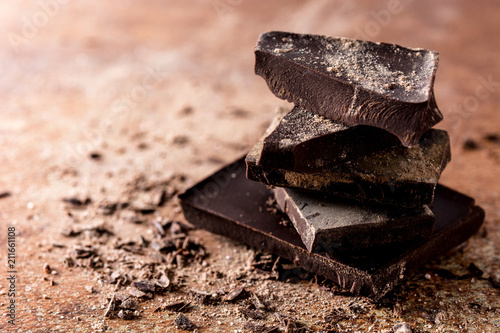 Broken chocolate pieces on brown background