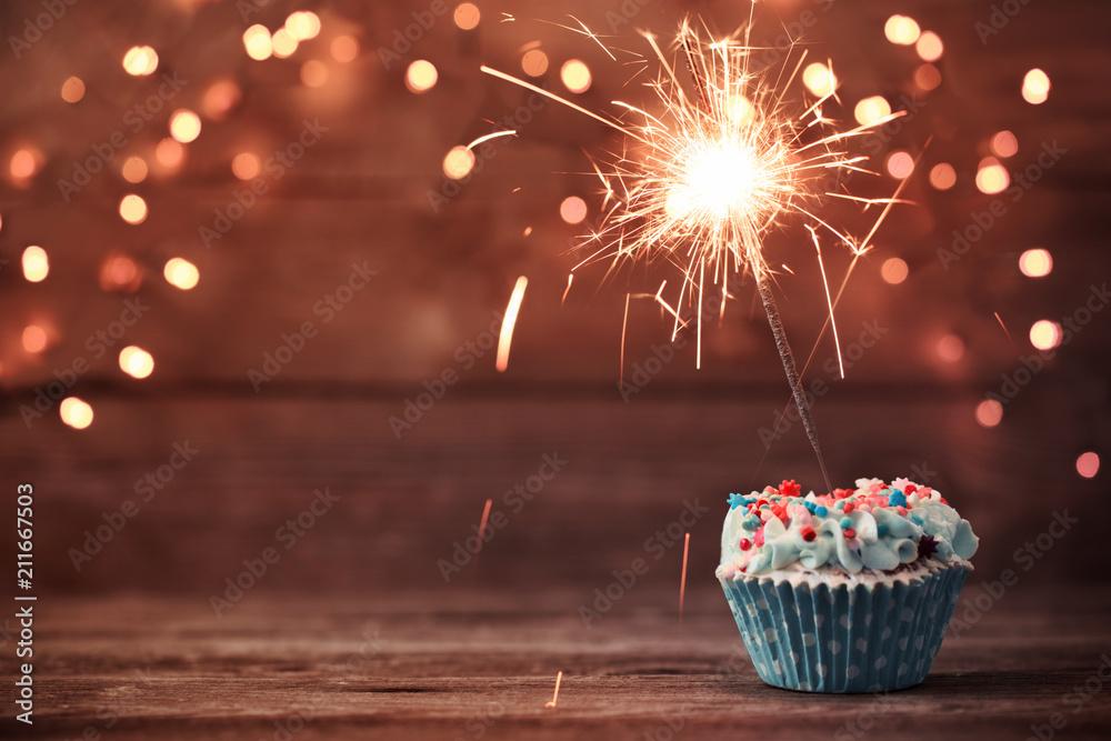 Fotografía cupcake with sparkler on old wooden background