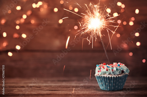 Stampa su Tela  cupcake with sparkler on old wooden background