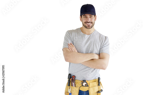 Obraz Portrait of young handyman standing at isolated white background with copy space. Successful repairman wearing baseball cap and tool belt. - fototapety do salonu