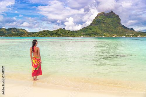 Carta da parati Tahiti luxury travel beach vacation woman walking in polynesian cover-up skirt beachwear on idyllic paradise island in French Polynesia