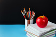 School accessories, notepad, pencils, markers, apple. Concept back to school on a blue background with copy space for text
