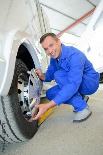 Fotografie, Obraz  Mechanic fitting hubcap to wheel
