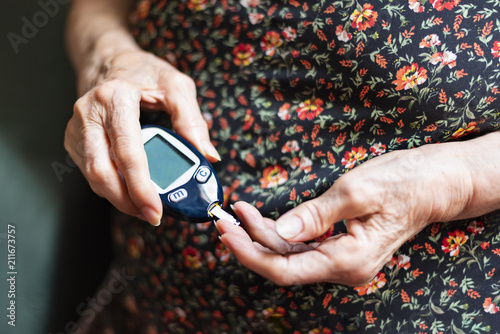 Fotografía  Old lady tracking her glucose levels. Health concept