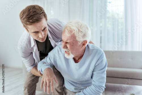 Fotografija Sudden dizziness. Kind man helping senior man who groaning