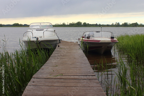 Fotobehang Pier Two white motor boats with cabin and open – moored at the jetty with the reeds in the evening on the background of the river and cloudy sky