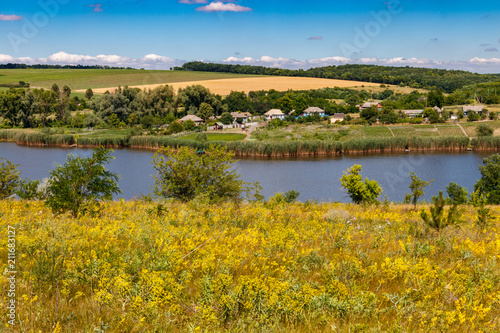 Summer landscape with beautiful lake, green meadows, hills, trees and blue sky
