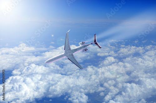 Fotografie, Obraz  Samolot odrzutowy nad chmurami schodzi do lądowania w promieniach słońca