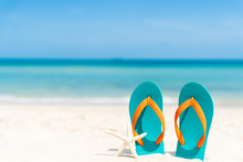 Beach Accessories Including Flip Flop, Starfish And Sea Shell On Sandy Beach, Green Sea And Blue Sky Background For Summer Holiday And Vacation Concept.