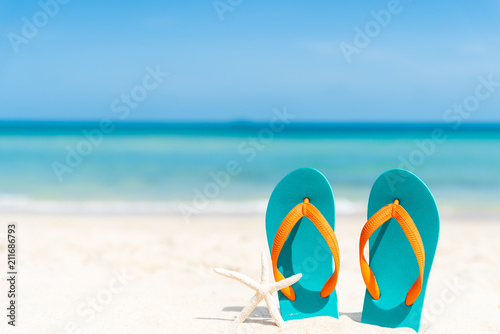 Obraz na plátně Beach accessories including flip flop, starfish and sea shell on sandy beach, green sea and blue sky background for summer holiday and vacation concept
