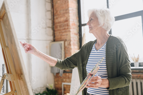 Waist up side view portrait of white haired senior woman holding palette painting pictures at easel in  art studio standing against windows in sunlight, copy space