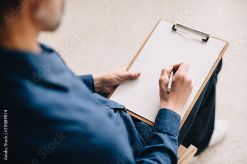 Warm toned closeup  of unrecognizable mature man holding blank sheet of paper ready to write or sketch pictures, copy space