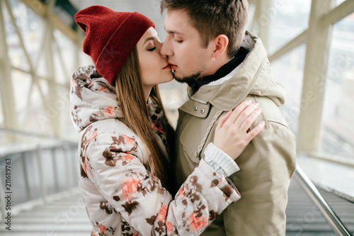 Lifestyle people. Young happy lovers embracing on meeting. Romantic pair of stylish cheerful hipsters hug. Girl in love. Happiness of loving youth couple. Emotional portrait of beautiful woman face.