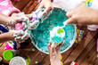 Leinwanddruck Bild - A group of young girls, children make a mess with frothy slime at a birthday party