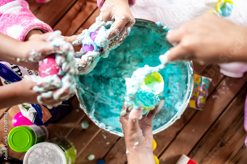 Fotomural A group of young girls, children make a mess with frothy slime at a birthday par