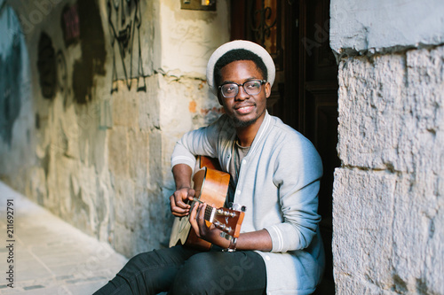 African musician playing guitar in the city - 211692791