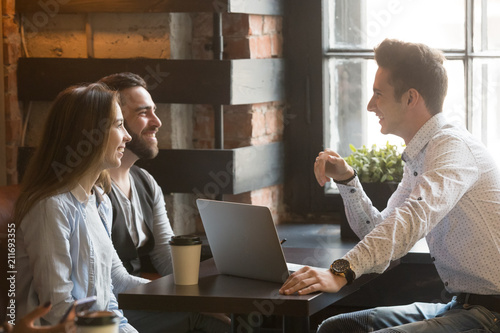 Male architect talking to smiling millennial couple, consulting on housing project, realtor explaining mortgage and contract condition to excited young couple during friendly meeting in coffee shop