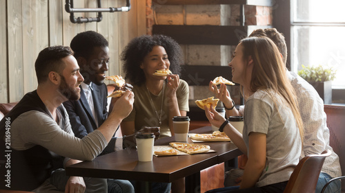 In de dag Kruidenierswinkel Smiling multiracial friends eating pizza and drinking coffee, laughing and having fun in restaurant, diverse millennial colleagues enjoying lunch during work break sitting at coffee table in loft cafe