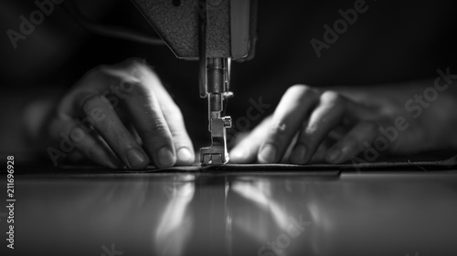 Fotografia, Obraz a man at work on a sewing machine. without a face.