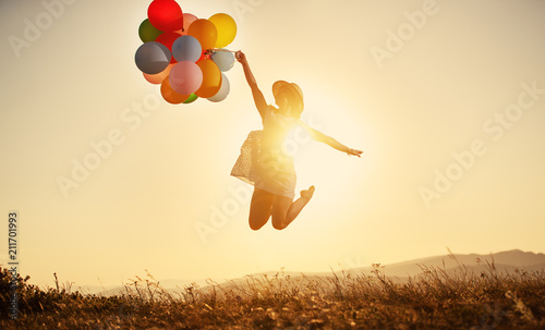 Obraz happy woman with balloons at sunset in summer - fototapety do salonu