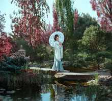 A Young Japanese Woman With Long, Black Hair Adorned With Kandzashi, Flowers And Long Hairpins With Crystal Beads Walks Near A Lake In A Fairy Garden Surrounded By Flowering Trees.