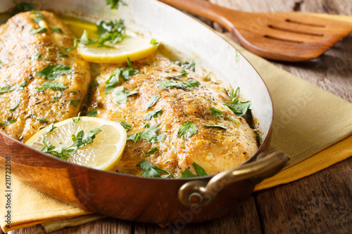 Fotografia Delicious fish: baked trout fillets with garlic buttery herb sauce, lemon and parsley close-up in a copper pan