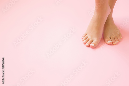 Fotobehang Pedicure Young, perfect groomed woman's feet on pastel pink background. Care about nails and clean, soft, smooth body skin. Pedicure and manicure beauty salon. Copy space. Empty place for text or logo.