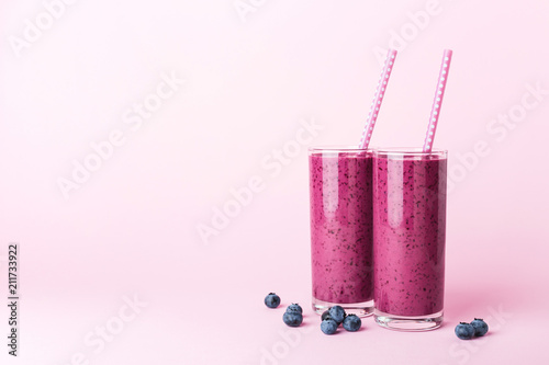 Carta da parati Two glasses of blueberries smoothie with straws on pink background
