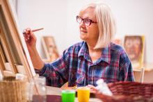 Elderly Woman Is Painting In H...