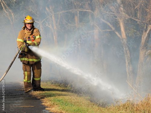 Melbourne, Australia - April 13, 2018: Fire fighter with a hose at a bush fire in an suburban area of Knox City in Melbourne east.