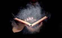 Hand Holding Mysterious Old Book, White Particle And Smoke Spread From Book