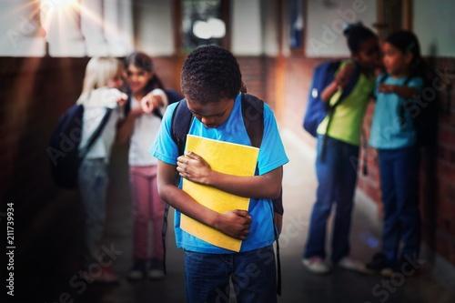 Sad pupil being bullied by classmates at corridor Wallpaper Mural