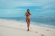 Slender tall girl model with smooth even skin and long hair strolls along the sand on her socks, straightens her hair with hair from the wind.